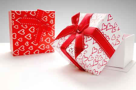 Two decorative gift boxes with red ribbon and hearts printed on white table. Front view. Grey background. Horizontal composition.