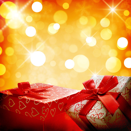 Two decorative gift boxes  with ribbon close up. Front view. Golden bokeh background.