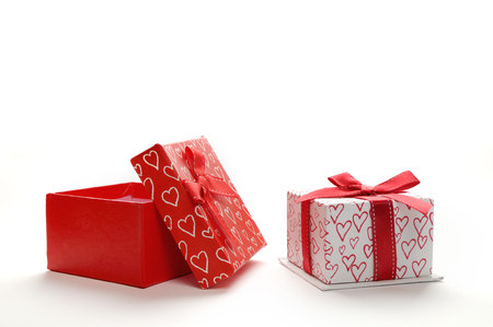 Two decorative gift boxes with red ribbon and hearts printed. Front view. White isolated background.