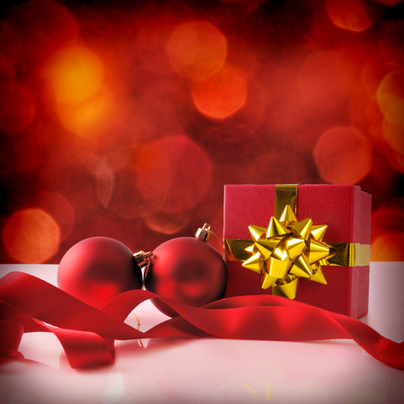 gold table cloth: Red Christmas decoration on a white table methacrylate. With gift box with gold ribbon, two balls and cloth tape. Front view. Square composition.