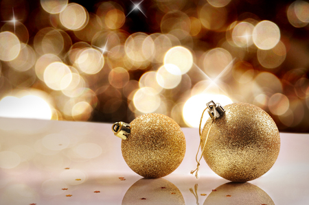 reflexive: Christmas concept with two gold Christmas balls on a white table methacrylate close up. Golden bokeh background with shiny stars. Front view. Horizontal composition. Stock Photo