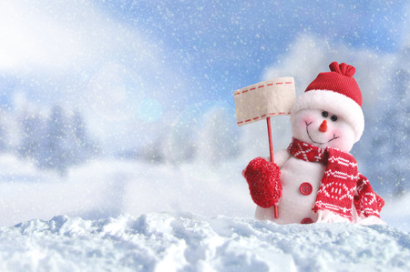 Winter arrival concept with Snowman with a blank placard in his hand. Dressed with red scarf and gloves and hat in the snow outside under the snow. Front view. Horizontal composition Archivio Fotografico