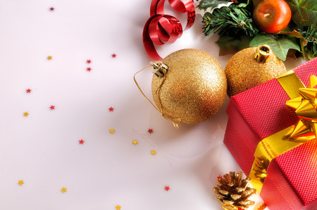reflexive: Christmas decoration on a white methacrylate table. Red gift box with gold ribbon, two golden balls and others objects. Top view. Horizontal composition.