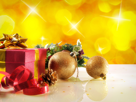 decoration objects: Yellow Christmas decoration on a white table methacrylate. With red gift box with gold ribbon, two golden balls and pearls. Front view. Horizontal composition.