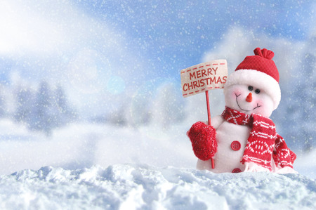 Snowman with a placard in his hand. Dressed with red scarf and gloves and hat in the snow outside announcing christmas under the snow. Front view. Horizontal composition