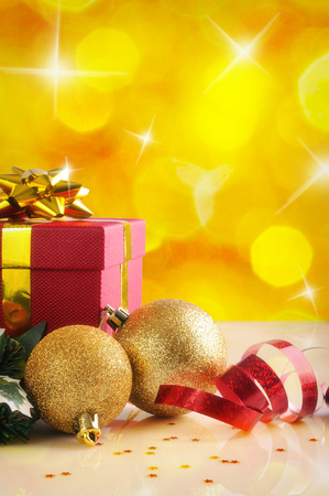 red bow: Yellow Christmas decoration on a white table methacrylate. With red gift box with gold ribbon, two golden balls and pearls. Front view. Vertical composition. Stock Photo