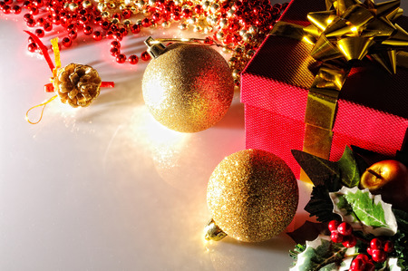 somberheid: Gloom Christmas decoration on a white methacrylate table. Red gift box with gold ribbon, two golden balls and pearls. Top view. Horizontal composition. Stockfoto