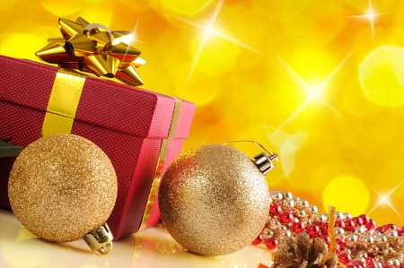 reflexive: Yellow Christmas decoration on a white table methacrylate. With red gift box with gold ribbon, two golden balls and pearls. Front view. Diagonal composition. Stock Photo