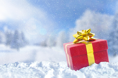 winter clothing: Gift box on snow at Christmas outside. Winter and snowy background. Front view. Horizontal composition