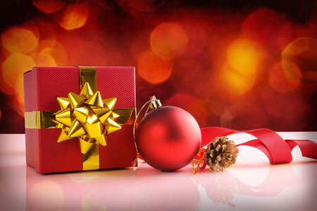 gold table cloth: Red Christmas decoration on a white table methacrylate. With gift box with gold ribbon, ball,pinecone and cloth tape. Front view. Horizontal composition. Stock Photo