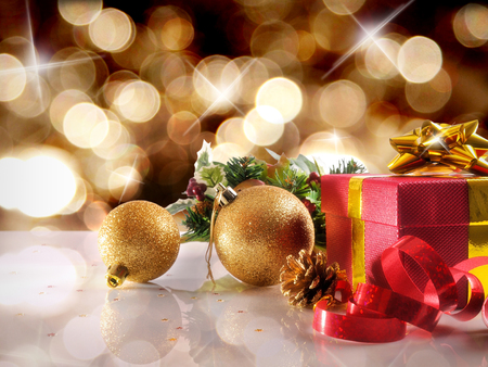 Golden Christmas decoration on a white table methacrylate. With red gift box with gold ribbon, two golden balls and pearls. Front view. Horizontal composition.