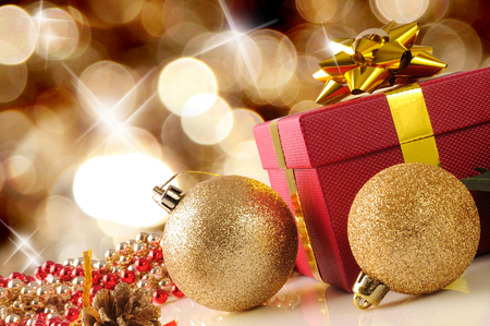reflexive: Golden Christmas decoration on a white table methacrylate. With red gift box with gold ribbon, two golden balls and pearls. Front view. Diagonal composition. Stock Photo