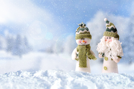 Winter arrival concept with two snowman dressed with green scarf and hat in the snow outside under the snow. Front view. Horizontal composition Imagens