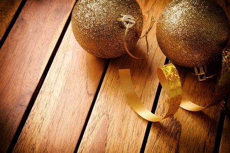 winter celebration: Golden Christmas decoration on table wooden slats. With ribbon and two golden balls. Top view. Horizontal composition. Stock Photo