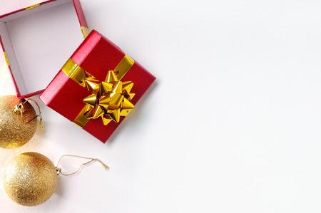 クリスマスの装飾は、左上に白を隔離しました。2 つの金球が付いている赤いギフト ボックス。平面図です。水平方向で構成。