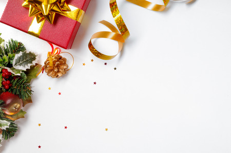 top: Christmas decoration isolated white on the left. Red and gift box and golden ribbon with floral ornament. Top view. Horizontal and diagonal composition.