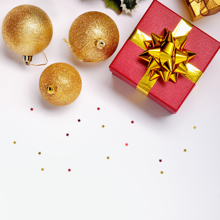new ball: Christmas decoration isolated white. Red and golden gift boxes with three golden ball, and floral ornament. Top view. Square composition. Stock Photo