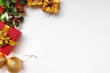 クリスマスの装飾は、左上に白を隔離しました。ゴールデン ボールと花飾りの赤と金色のギフト ボックス。平面図です。水平方向で構成。