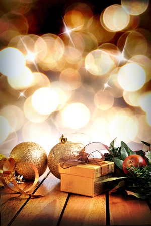 ribbon: Golden Christmas decoration on a wooden table. Golden gift box, two golden balls and floral ornament with bokeh background with stars. Front view. Vertical composition. Stock Photo