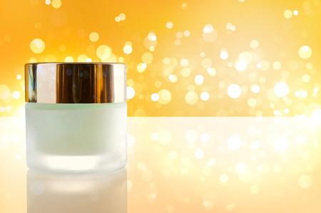 cuerpo humano: Vidrio cerrado frasco con crema hidratante facial o corporal en el cuadro blanco. Vista frontal. Composici�n horizontal. Bokeh de fondo amarillo.