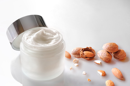 almond: Glass open jar with facial or body almond moisturizer jar open with almonds on the table. Top view. Horizontal composition. White isolated.
