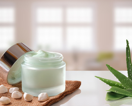 Glass open jar with facial or body cream aloe vera on burlap. With lid, small stones and aloe plant.Windows background. Front view.