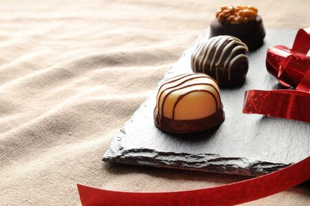 bonbons: Assorted bonbons black and white chocolate with nuts and red ribbon on a slate plate in a table with brown tablecloth fabric. Elevated view. Close up. Horizontal composition. Stock Photo