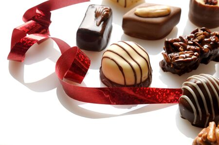 Assorted bonbons black and white chocolate with nuts and red ribbon on a white table. Elevated view. Close up. Horizontal composition.