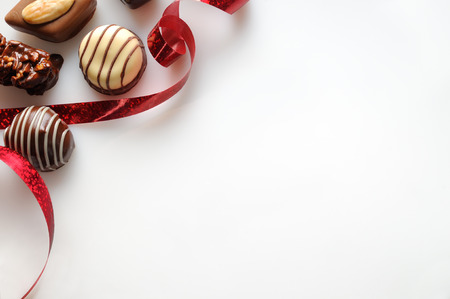 red square: Assorted bonbons black and white chocolate with nuts and red ribbon on a white table. Top view. Close up. Horizontal composition.