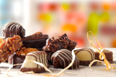 bonbons: Group of bonbons stacked. Black and white chocolate with nuts and straw decoration on a table with brown tablecloth fabric with colorfull background. Front view. Horizontal composition. Stock Photo