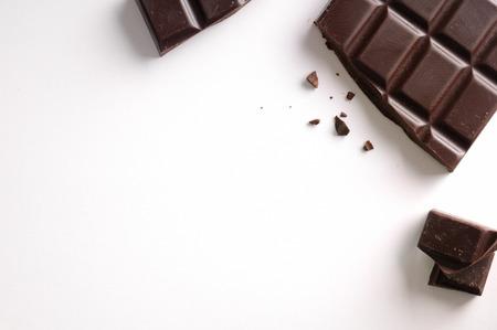 Broken chocolate bar isolated on white table. Horizontal composition. Top view Foto de archivo