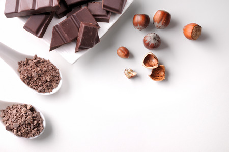 Portions and chocolate chips with hazelnuts on a white porcelain container on a white wooden table isolated. Horizontal composition. Top view