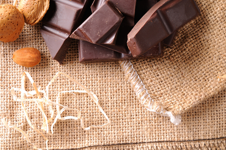 heap up: Heap of artisan portions chocolate on burlap sack with almonds with straw decoration. Horizontal composition. Top view. Close up. Stock Photo