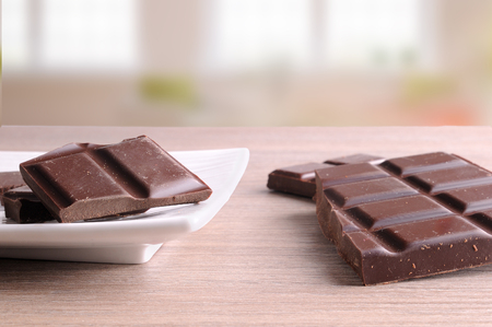 front view: Tablet and portions of chocolate in a white porcelain dish on a brown wooden table in a living room. Horizontal composition. Front view Stock Photo