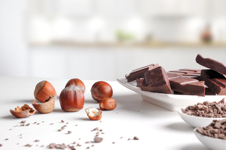 Portions and chocolate chips with hazelnuts on a white porcelain container on a white table in kitchen. Horizontal composition. Front view Foto de archivo