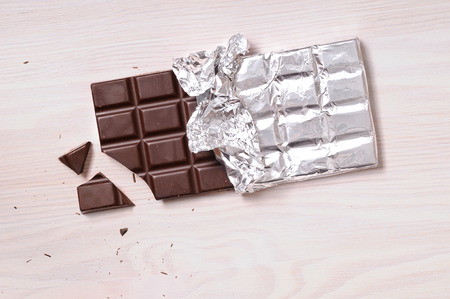 horizontal bar: Chocolate bar with silver wrapping on a wooden table with a broken portion. Horizontal composition. Top view Stock Photo