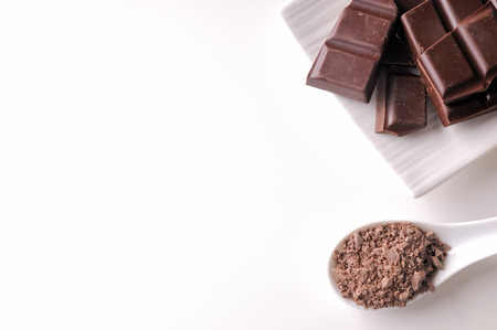 Portions and chocolate chips on a white porcelain container on a white wooden table isolated. Horizontal composition. Top view