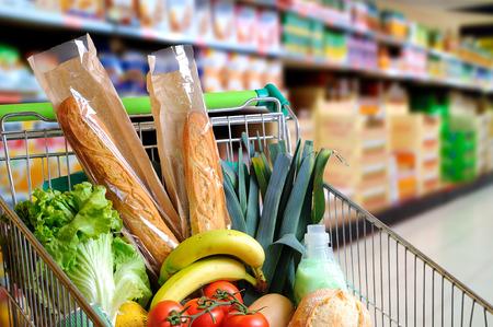 Winkelwagentje vol met voedsel in de supermarkt gangpad. Hoge interne uitzicht. horizontale samenstelling Stockfoto