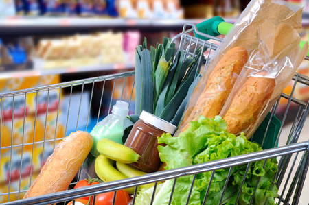 Shopping cart full of food in the supermarket aisle. Side view. Horizontal composition