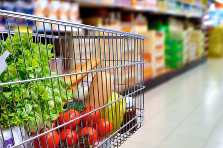 tiendas de comida: Cesta de la compra lleno de comida en el pasillo de un supermercado. opinión de la inclinación lateral. composición horizontal