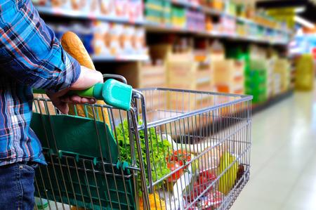Man duwen winkelwagentje vol met voedsel in de supermarkt gangpad. Verhoogde zicht naar achteren. horizontale samenstelling