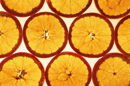 Pattern of group of orange slices against the light. Close up.Top view Stock Photo