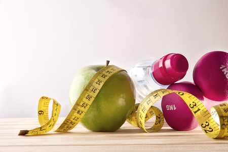 Dumbbells with apple, mineral water bottle and tape measure on wood table and isolated background. Concept women lifestyle, health, diet and sports. Horizontal composition. Front view
