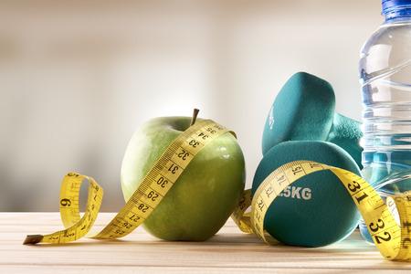 salud y deporte: Pesas con manzana, botella de agua mineral y cinta métrica en la mesa de madera y fondo gimnasio. Concepto de estilo de vida, la salud, la dieta y los deportes. Composición horizontal. Vista frontal