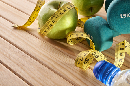 kilos: Green dumbbells, apple and tape measure on wooden floor. Concept health, diet and sports. Horizontal composition. Elevated view