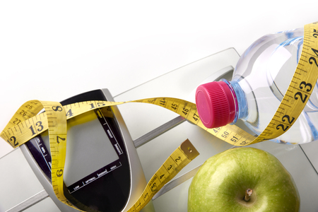 Scale with mineral water, apple and tape measure isolated. Concept health, diet and nutrition. Horizontal composition. Top view Stock Photo