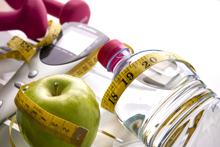 Scale with dumbbells, mineral water, apple and tape measure isolated. Concept health, diet and sport. Horizontal composition. Top elevated view