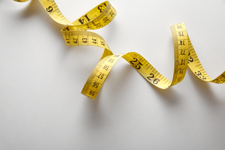inches: Yellow tape measure in meters and inches in a spiral on white table. Top view. Horizontal composition. Stock Photo
