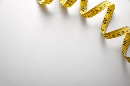 nombres: ruban � mesurer jaune en m�tres et en pouces dans une spirale sur la table blanche. Vue de dessus. Composition horizontale.