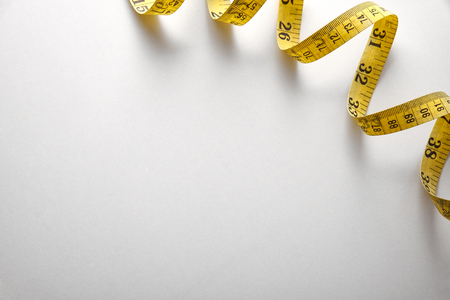 in number: Yellow tape measure in meters and inches in a spiral on white table. Top view. Horizontal composition. Stock Photo
